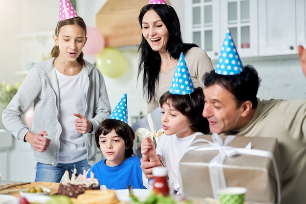 Joyeuse famille latine avec des enfants portant des casquettes d'anniversaire, célébrant l'anniversaire ensemble à la maison. famille heureuse, concept de célébration. mise au point sélective
