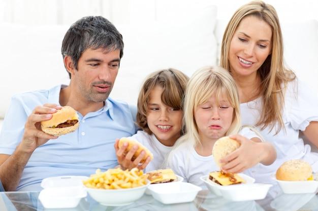 Joyeuse famille mangeant des hamburgers