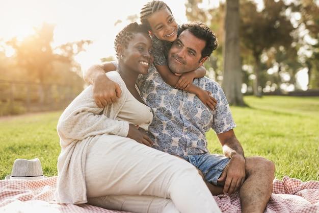 Joyeuse famille multiraciale s'embrassant au parc de la ville - une femme enceinte africaine avec un mari caucasien et un enfant métis profitent d'un pique-nique en plein air