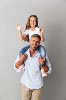 Joyeuse famille souriant tandis que petite fille s'amusant et assise sur le cou de son père heureux, isolé sur gris