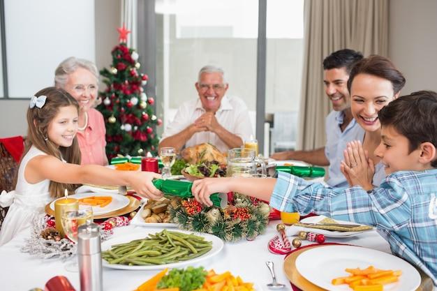Joyeuse famille à la table à manger pour le dîner de noël dans la maison