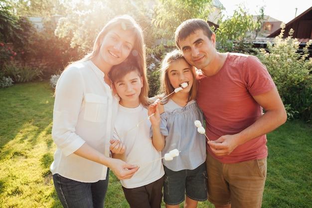 Joyeuse famille tenant une brochette de guimauve et regardant la caméra
