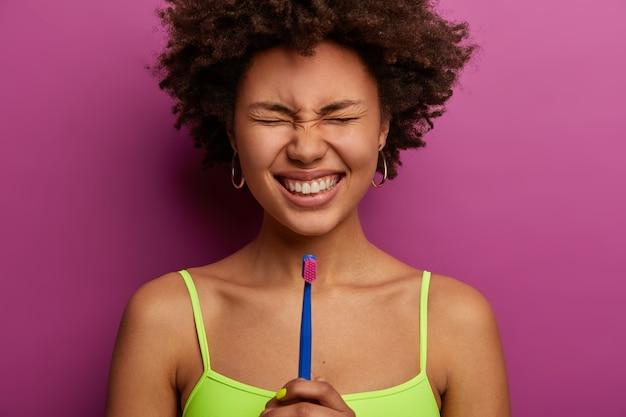 Joyeuse femme adulte aux cheveux bouclés sourit largement, montre des dents bien soignées parfaites
