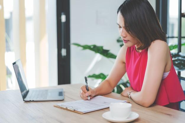 Une joyeuse femme d'affaires asiatique d'âge moyen en tenue décontractée et décontractée travaillant à la maison, vérifiant ses e-mails sur un ordinateur portable, écrivant sur du papier de document de comptabilité financière. stock photo