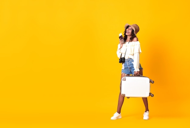 Joyeuse femme africaine vêtue de vêtements d'été tenant un passeport avec billet