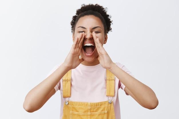 Joyeuse femme afro-américaine insouciante en salopette jaune, tenant les paumes autour de la bouche ouverte, criant, appelant quelqu'un à distance