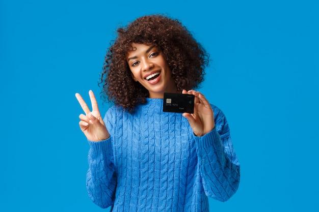 Joyeuse femme afro-américaine mignonne avec coupe de cheveux afro, tête inclinée montrer signe de paix