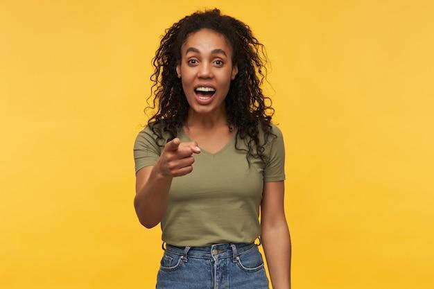 Joyeuse femme afro-américaine positive, porte un t-shirt vert et un pantalon en jean, rit et pointe du doigt vers vous
