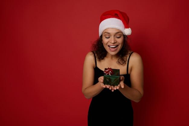 Joyeuse femme afro-américaine se sentant heureuse en regardant une petite belle boîte-cadeau de noël dans ses mains, isolée sur fond rouge avec espace de copie pour l'annonce. concept de nouvel an et joyeux noël.