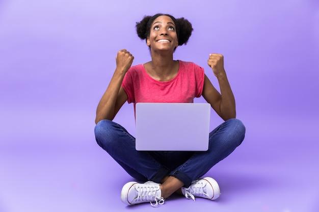 Joyeuse femme afro-américaine souriant et à l'aide d'un ordinateur portable d'argent, assis sur le sol avec les jambes croisées, isolé