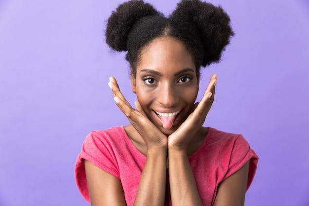 Joyeuse femme afro-américaine souriant et touchant son visage, isolé