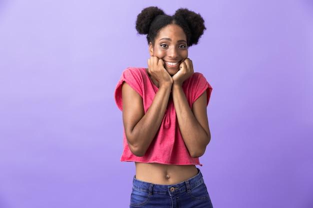 Joyeuse femme afro-américaine souriant et touchant le visage, isolé