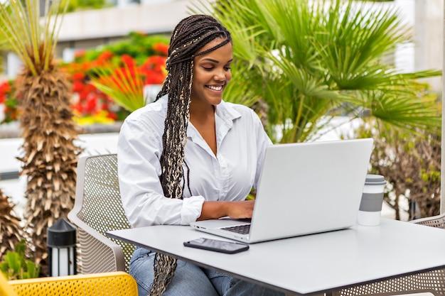 Joyeuse femme afro-américaine utilisant un ordinateur portable dans un café à l'extérieur avec un arrière-plan flou de plantes. femme avec des tresses assis à l'aide d'un ordinateur portable au café.
