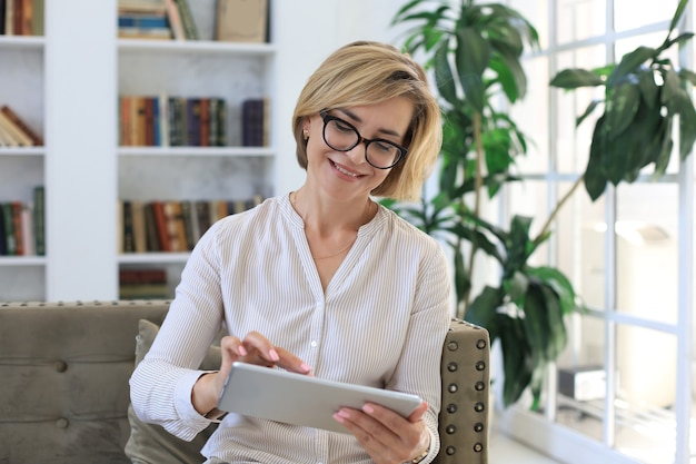 Joyeuse femme d'âge moyen assise sur un canapé, utilisant des applications pour tablettes informatiques, regardant l'écran, lisant de bonnes nouvelles sur les réseaux sociaux, faisant des achats ou discutant en ligne.