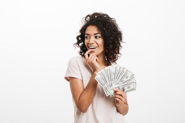 Joyeuse femme américaine avec une coiffure afro et grand sourire tenant un ventilateur d'argent en dollars, isolé sur un mur blanc