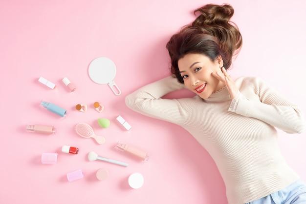 Joyeuse femme asiatique allongée sur le sol rose avec ses outils de maquillage cosmétique