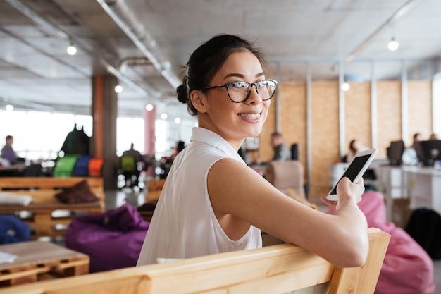 Joyeuse femme asiatique assise et utilisant un téléphone mobile à écran blanc