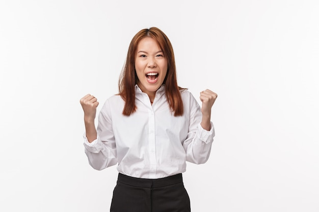 Joyeuse femme asiatique chanceuse réussie remportant le prix, la loterie debout sur le mur blanc pompe les poings et crie oui de joie, triomphant de la victoire, devient champion ou gagnant sur le mur blanc