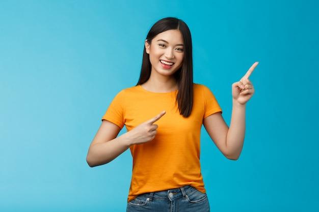Joyeuse femme asiatique mignonne et animée souriante riant optimiste, pointant le coin supérieur droit, donner des conseils sur ce que choisir, faire des achats en ligne, souriant joyeusement, promo enthousiaste, fond bleu
