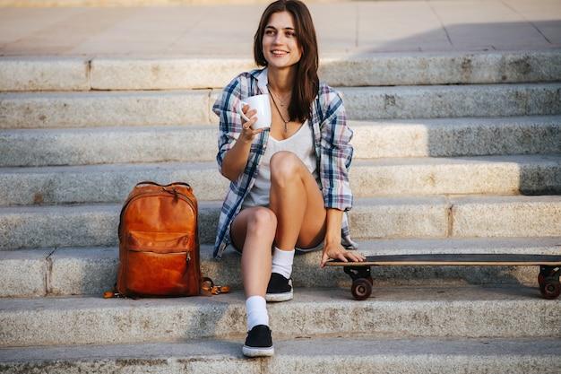 Joyeuse femme assise dans les escaliers à côté de sa planche à roulettes se reposant