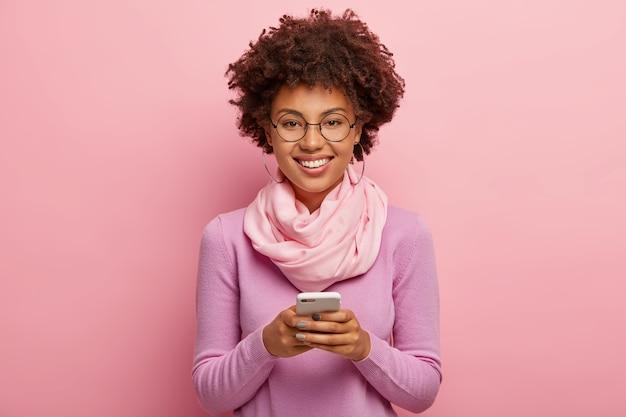 Joyeuse femme attrayante souriante joue à des jeux sur une application de téléphone mobile
