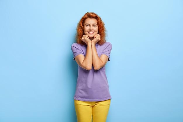 Joyeuse femme au gingembre tient le menton, sourit doucement, étant de bonne humeur