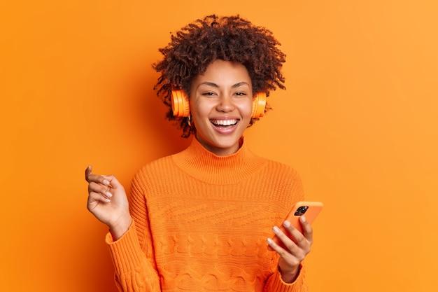 Joyeuse femme aux cheveux bouclés détient smartphone moderne soulève largement la main sourit