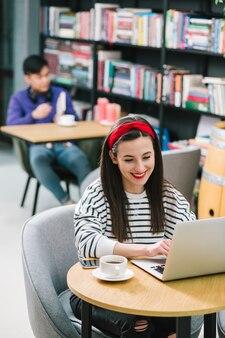 Joyeuse femme aux cheveux longs assise à la table avec une tasse de café et regardant l'écran avec un sourire aimable