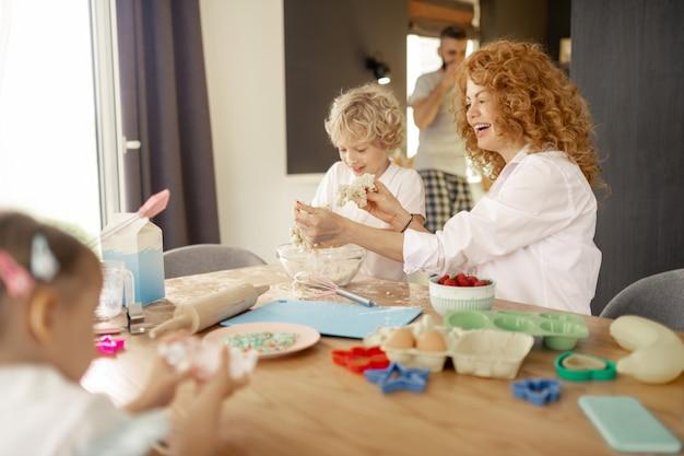 Joyeuse femme aux cheveux rouges tenant un morceau de pâte