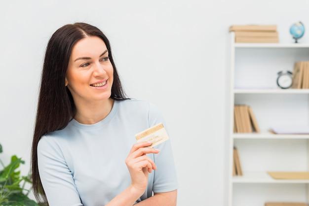 Joyeuse femme en bleu debout avec carte de crédit au bureau
