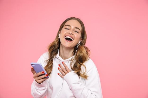Joyeuse femme blonde portant des vêtements décontractés écoutant de la musique les yeux fermés sur un mur rose