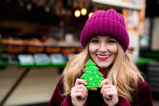 Joyeuse femme blonde tenant du pain d'épice de noël sucré, posant sur le fond de décoration lumineuse