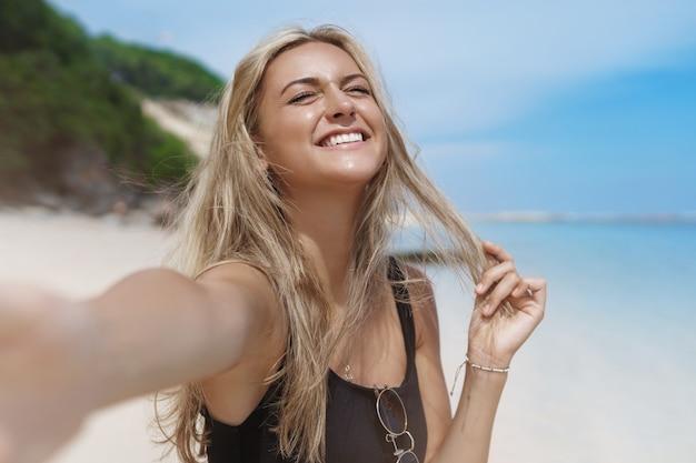 Joyeuse femme bronzée blonde insouciante heureuse jouit du soleil, ferme les yeux et prend selfie dans la plage de sable