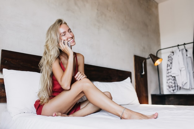 Joyeuse femme bronzée avec une coiffure longue, parler au téléphone dans sa chambre. superbe femme souriante assise sur le lit et appelant quelqu'un.