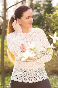 Joyeuse femme brune au maquillage nude, vêtue d'un chemisier en dentelle, posant près des fleurs de magnolia en fleurs