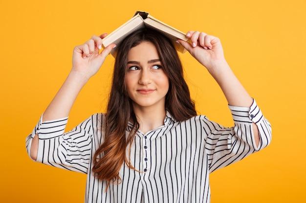 Joyeuse femme brune en chemise tenant un livre sur la tête