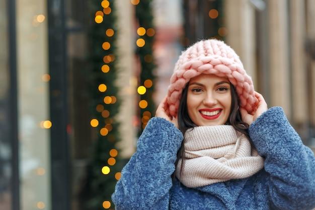 Joyeuse femme brune en manteau marchant dans la ville en hiver. espace libre