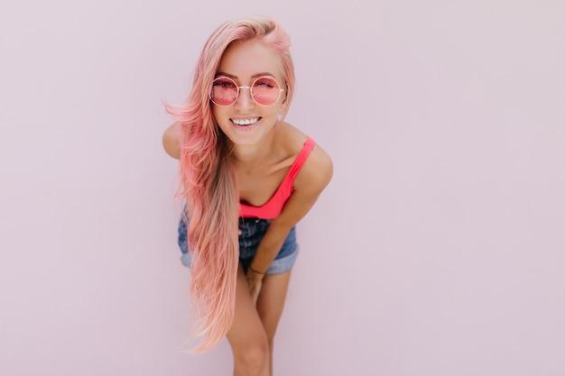 Joyeuse femme caucasienne aux cheveux roses posant avec un sourire mignon.