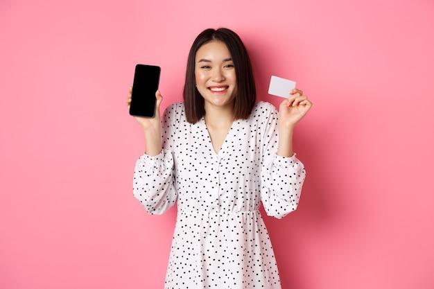 Joyeuse femme coréenne montrant l'écran d'un smartphone et une carte de crédit payant pour une commande internet démontrant...