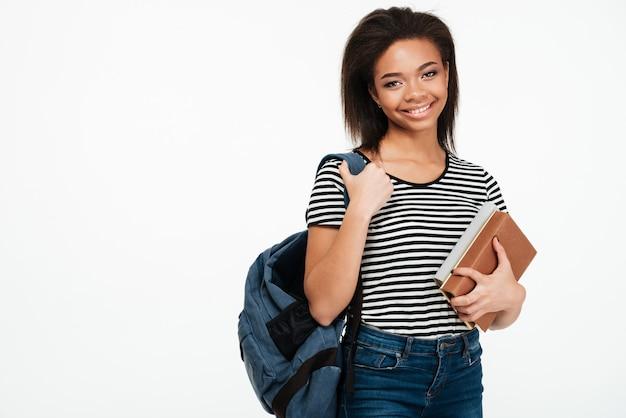 Joyeuse femme étudiante africaine souriante portant un sac à dos et tenant des livres