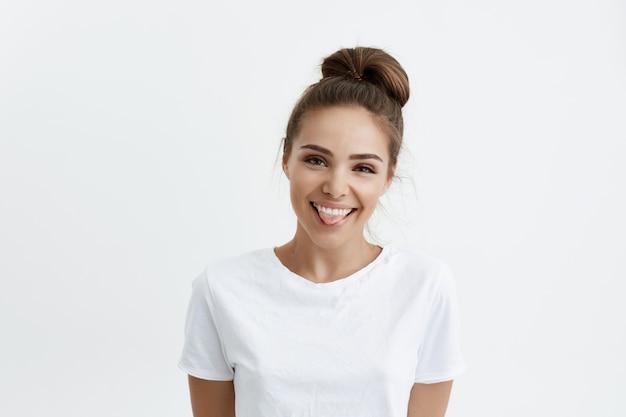 Joyeuse femme européenne attrayante avec une coiffure élégante montrant la langue et souriant, étant de bonne humeur