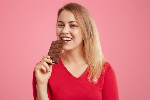 Joyeuse femme européenne détient une barre de chocolat