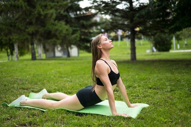 Joyeuse femme exerçant dans le parc