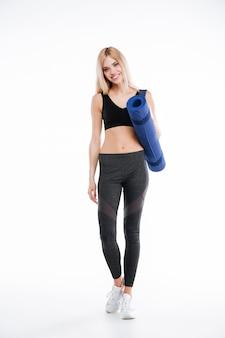 Joyeuse femme fitness tenant un tapis de sport