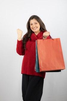 Joyeuse femme heureuse appréciant les sacs à provisions.