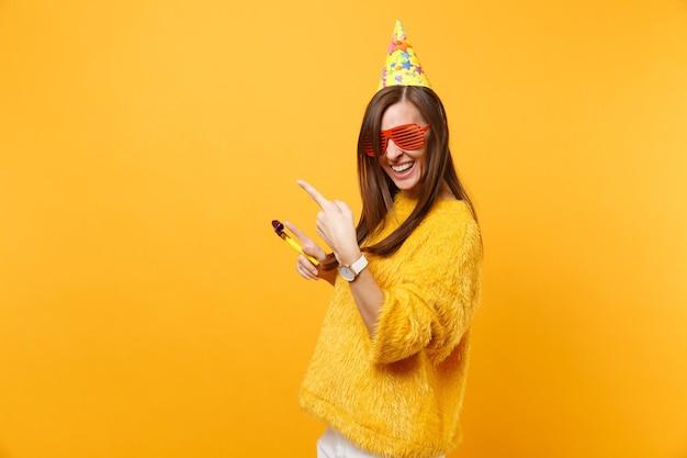 Joyeuse femme heureuse dans des lunettes orange drôles, chapeau d'anniversaire avec pipe en train de pointer les index de côté sur l'espace de copie, célébrant isolé sur fond jaune. les gens émotions sincères, mode de vie.