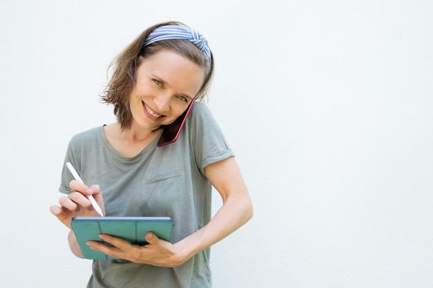 Joyeuse femme heureuse écrit sur l'écran de la tablette