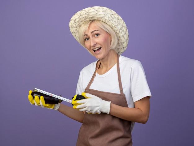 Joyeuse femme jardinière blonde d'âge moyen en uniforme portant un chapeau et des gants de jardinage mesurant l'aubergine avec un mètre ruban