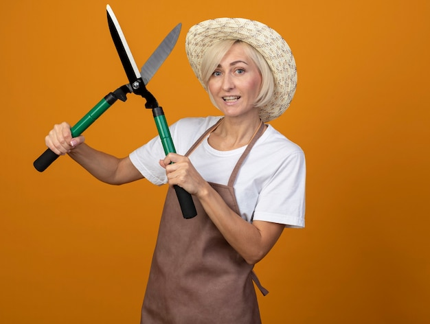 Joyeuse femme jardinière blonde d'âge moyen en uniforme portant un chapeau tenant des cisailles à haies isolées sur un mur orange avec espace pour copie