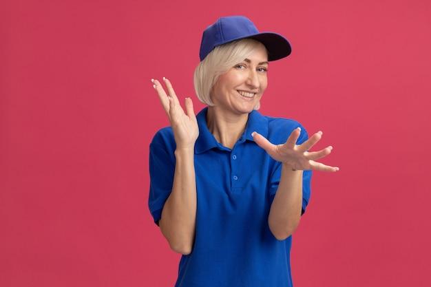 Joyeuse femme de livraison blonde d'âge moyen en uniforme bleu et casquette écartant les mains